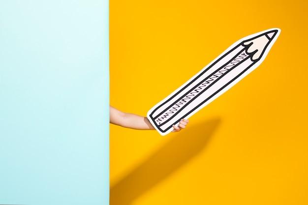 Portrait d'écolière avec un gros crayon Photo gratuit