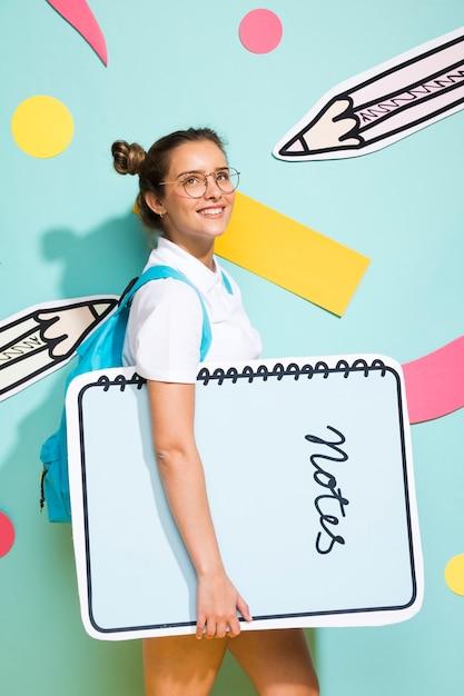 Portrait d'écolière avec gros modèle de bloc-notes Photo gratuit