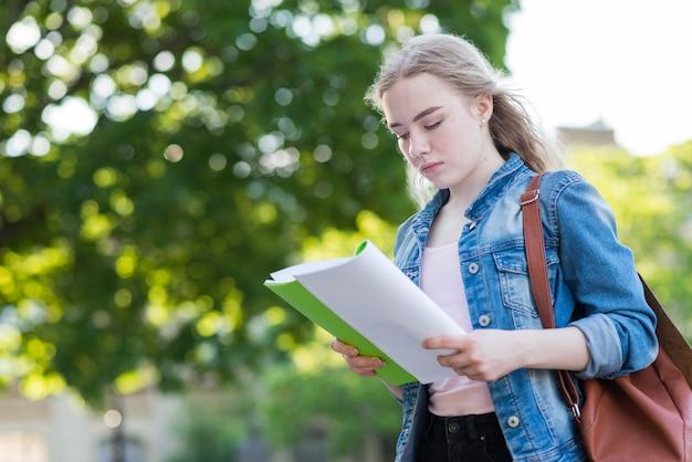 Portrait d'écolière avec livre et sac Photo gratuit