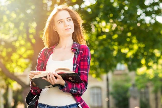Portrait d'écolière avec des livres dans le parc Photo gratuit