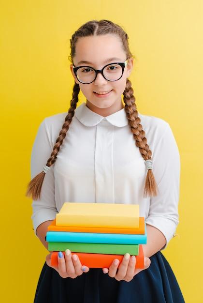 Portrait, écolière, lunettes, livres, manuels, jaune bleu Photo Premium