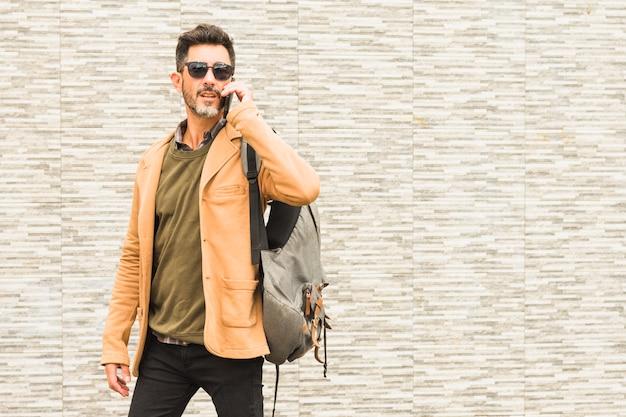 Portrait, élégant, homme, debout, contre, mur, à, son sac à dos, parler, sur, téléphone portable Photo gratuit