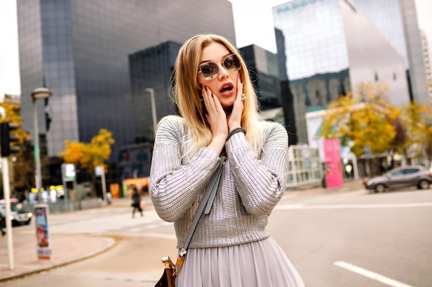 Portrait élégant De Rue De Femme Blonde Portant Une Tenue Grise Glamour à Mettre La Main à Ses Lunettes De Soleil, Centre D'affaires. Visage Surpris. Photo gratuit