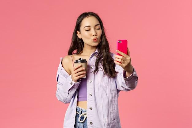 Portrait D'une élégante Blogueuse, Influenceuse Internet De Style De Vie Prenant Un Selfie Avec Du Café à Emporter De Son Café Préféré, Tenez Votre Téléphone Portable, Faites La Moue Pour L'embrasser Et Fermez Les Yeux Photo Premium