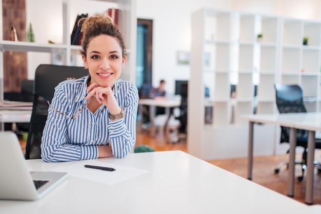 Portrait d'un employé de bureau féminin souriant beau assis sur le lieu de travail. Photo Premium