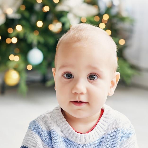 Portrait d'enfant bébé avec l'arbre de noël. tout-petit mignon de noël. concept de vacances en famille. salle de jeux pour enfants. noël dans la chambre des enfants. Photo Premium