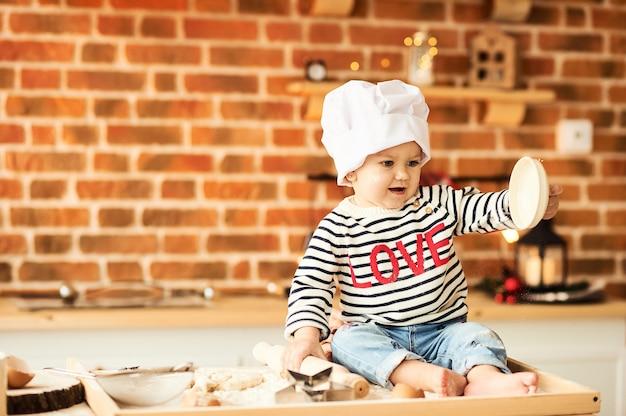 Un Portrait D'enfant Mignon Cuisiné Et Joué Avec De La Farine Et De La Pâte Dans La Cuisine Photo Premium
