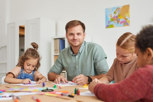 Portrait De L'enseignant De Sexe Masculin Souriant Tout En Travaillant Avec Un Groupe Multiethnique D'enfants Dessinant Des Images Pendant Les Cours D'art à L'école Ou Au Centre De Développement Photo Premium