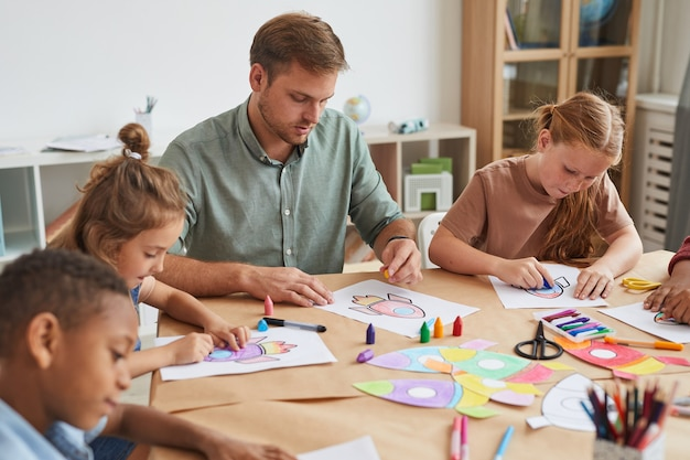 Portrait D'un Enseignant Travaillant Avec Un Groupe Multiethnique D'enfants Dessinant Des Images Pendant La Classe D'art à L'école Ou Dans Un Centre De Développement Photo Premium