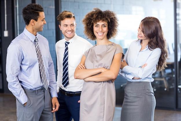 Portrait, équipe affaires confiant, debout, dans, bureau, mains ont croisé Photo Premium