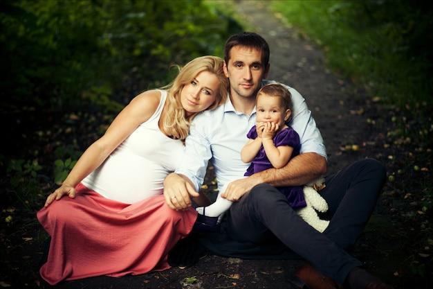 Portrait d'été de famille heureuse. femme enceinte, père et petite fille. Photo Premium