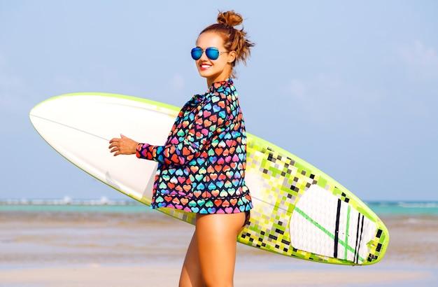 Portrait D'été En Plein Air De Femme Souriante En Cours D'exécution Avec Planche De Surfeur Près De L'océan Bleu Photo gratuit