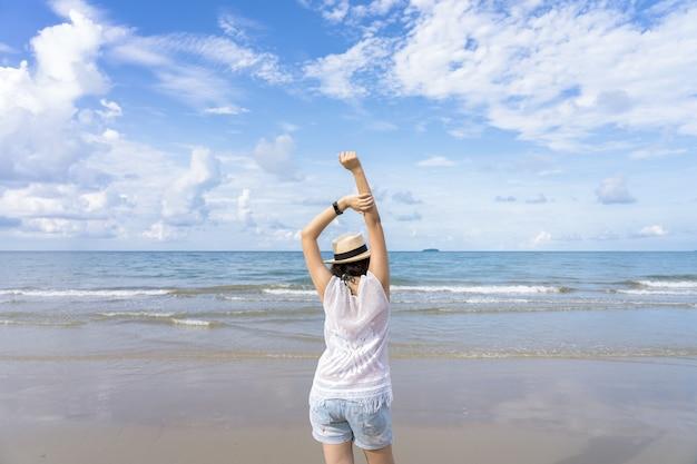 Portrait d'été en plein air de jeune femme asiatique portant un chapeau élégant et des vêtements se tenant debout sur la plage Photo Premium