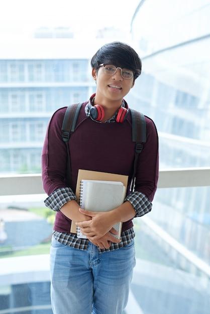 Portrait d'un étudiant asiatique posant avec des livres d'étude sur le balcon de l'école Photo gratuit