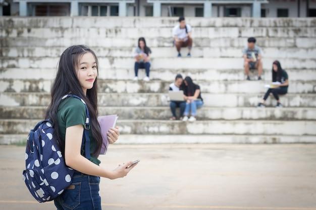 Portrait d'étudiant féminin tenant des livres. adolescents lycéens à l'extérieur Photo Premium