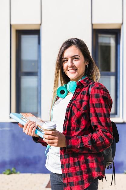 Portrait d'un étudiant souriant tenant des livres et une tasse de café jetable dans la main à la recherche d'appareil photo Photo gratuit
