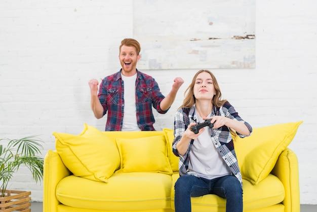 Portrait, excité, jeune, homme, debout, derrière, femme, jeu vidéo, chez soi Photo gratuit