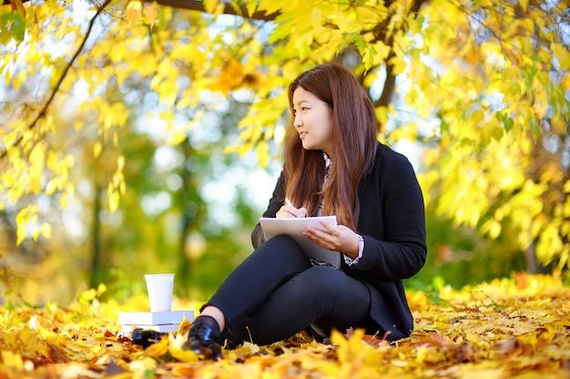 Portrait en extérieur belle étudiante asiatique fille. jeune femme étudiant / travaillant et profitant d'une belle journée d'automne ensoleillée Photo Premium