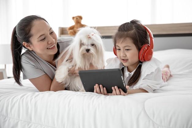 Portrait De Famille Amoureuse Avec Des Loisirs De Chien Caniche Blanc Et écouter De La Musique Sur Le Lit Dans La Chambre. Photo Premium
