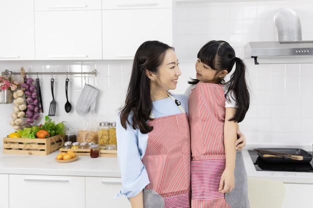 Portrait de famille asiatique portant des tabliers dans la cuisine Photo Premium