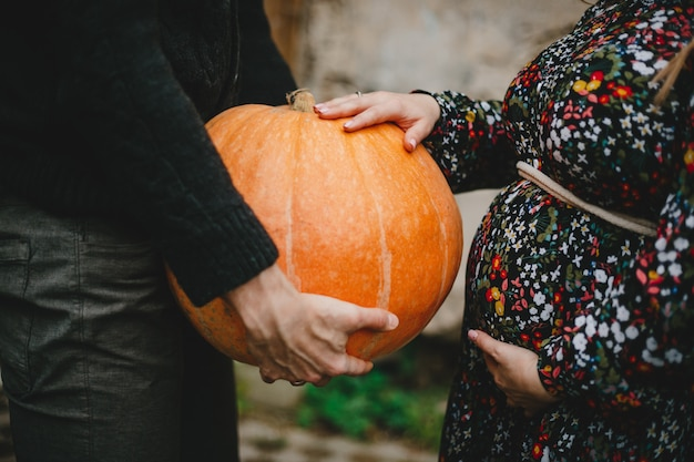 Portrait de famille. charmant couple enceinte pose à l'extérieur Photo gratuit