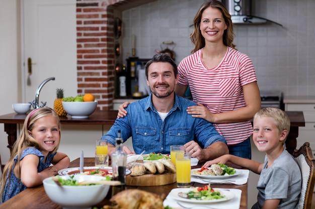 Portrait de famille heureuse ayant un repas dans la cuisine Photo Premium