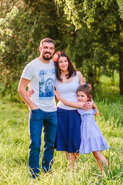 Portrait de famille heureuse, debout ensemble dans le parc Photo gratuit