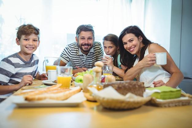 Portrait De Famille Heureuse Prenant Son Petit Déjeuner Ensemble Photo Premium