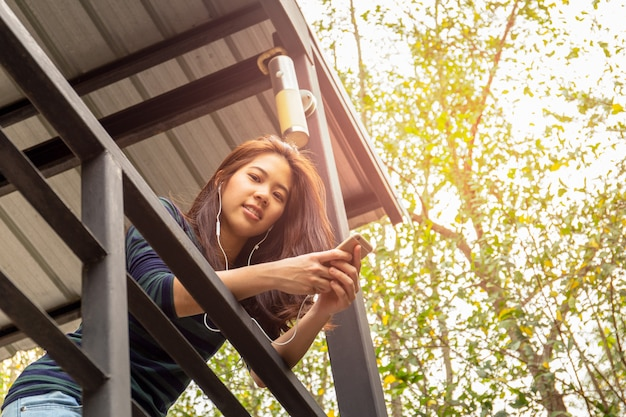 Portrait de femme adolescente asiatique des années 20 écouter de la musique avec des écouteurs. Photo Premium