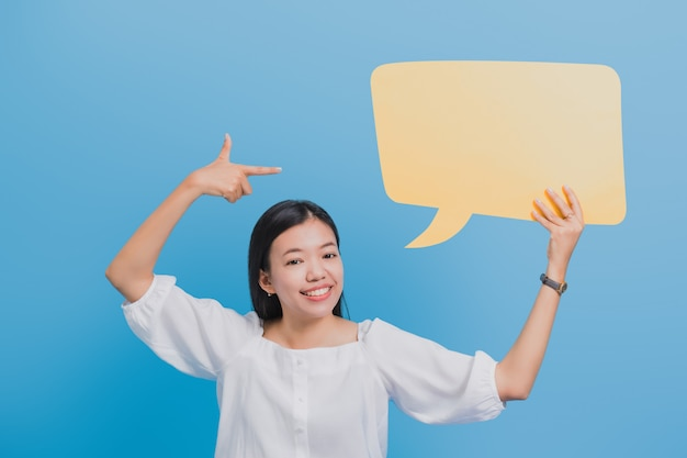 Portrait de femme d'affaires asiatique belle confiant debout et tenant discours de bulle jaune vide. Photo Premium