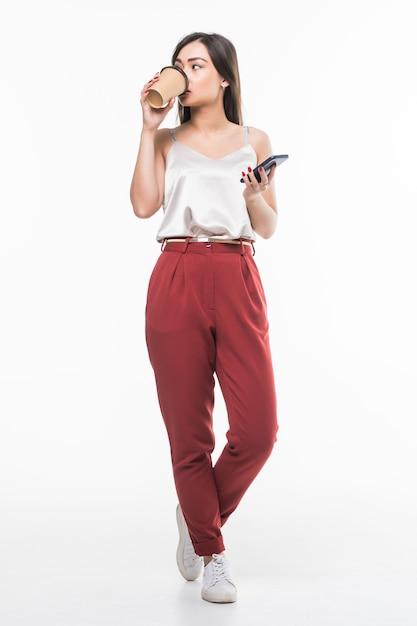 Portrait D'une Femme D'affaires Asiatique Souriante à L'aide De Téléphone Portable Tout En Tenant Une Tasse De Café Pour Aller Isolé Sur Mur Blanc Photo gratuit