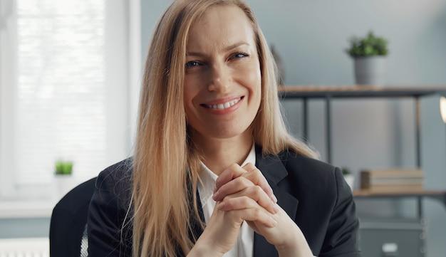 Portrait De Femme D'affaires Blonde Souriante En Costume Classique Assis Avec Les Mains Jointes Regardant La Caméra Photo Premium
