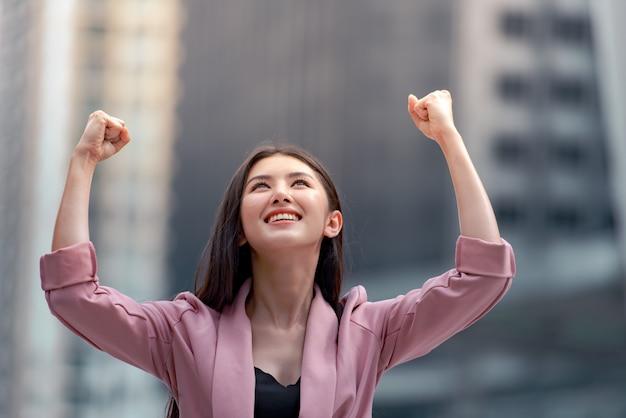 Portrait d'une femme d'affaires confiant, souriant et leva les mains vers le haut sur un fond de ville. Photo Premium