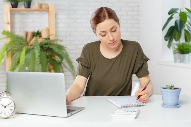Portrait d'une femme d'affaires décontractée heureux assis sur son lieu de travail au bureau Photo Premium