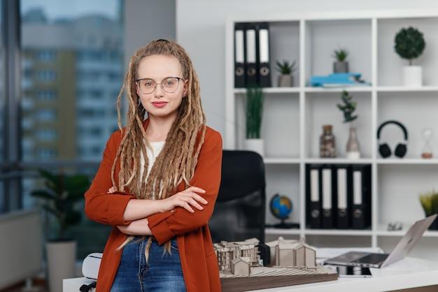 Portrait D'une Femme D'affaires élégante Avec Des Dreadlocks Près De Son Lieu De Travail Avec Maquette Du Futur Bâtiment. Photo Premium