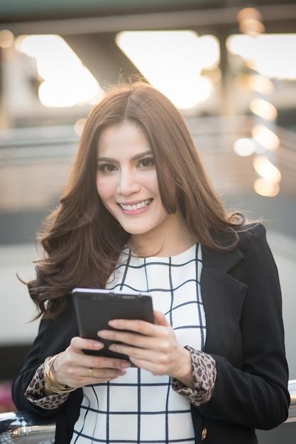 Portrait de femme d'affaires intelligente réussie à la recherche de confiance et souriant tenant une tablette Photo Premium