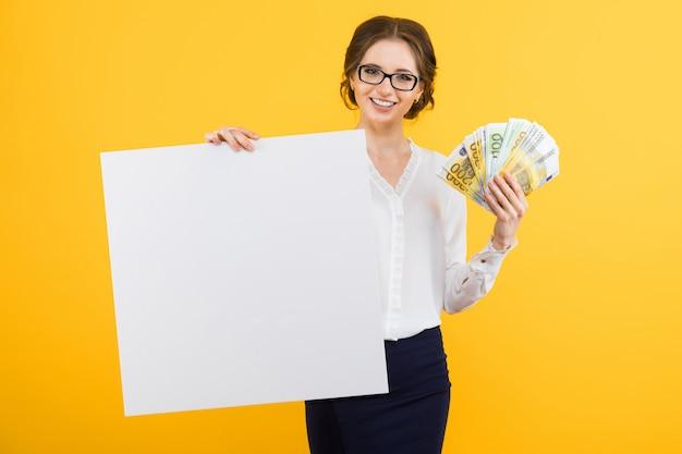 Portrait de femme d'affaires jeune confiant beau avec de l'argent dans ses mains et panneau d'affichage vide sur jaune Photo Premium