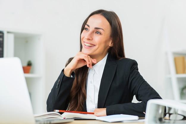 Portrait de femme d'affaires jeune heureux assis au lieu de travail rêver Photo gratuit