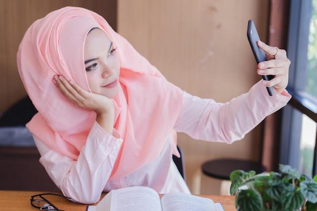Portrait de femme d'affaires musulmane asiatique prendre une photo par elle-même. femme d'affaires musulmane asiatique selfie. Photo Premium