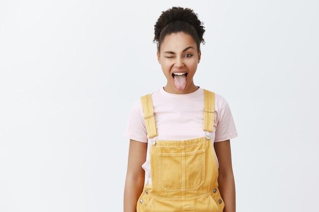 Portrait De Femme Afro-américaine Heureuse Insouciante En Salopette Jaune Sur T-shirt à La Mode, Sticking Out Tongue Et Clignant Des Yeux Joyeusement Photo gratuit