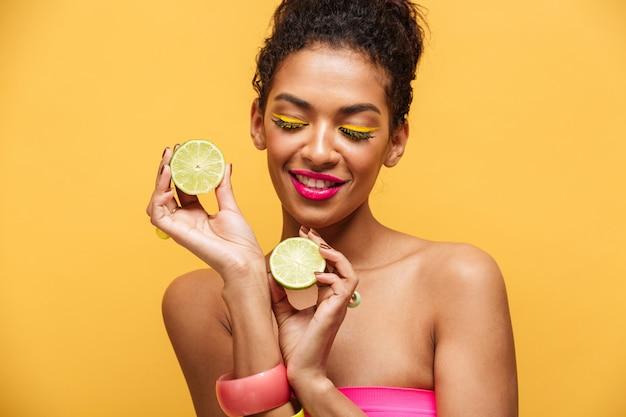 Portrait De Femme Afro-américaine Heureuse Avec Maquillage Tendance Tenant Deux Moitiés De Citron Vert Frais Dans Les Deux Mains, Isolé Sur Mur Jaune Photo gratuit