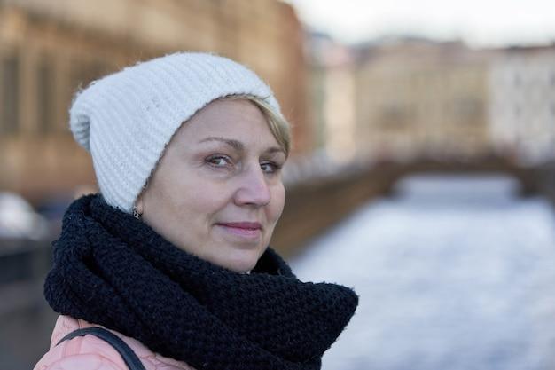 Portrait D'une Femme D'âge Moyen Dans Un Foulard Noir Et Un Chapeau Blanc Dans Le Contexte D'un Front De Mer Floue Photo Premium