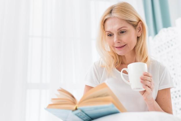 Portrait, De, Femme Aînée, Lecture Livre, Dans Lit Photo Premium
