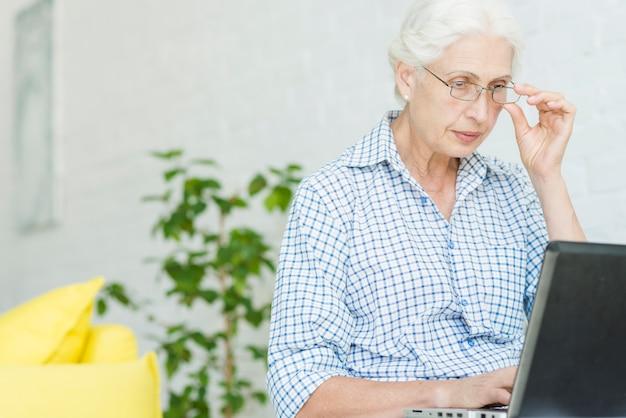 Portrait, femme aînée, regarder, ordinateur portable Photo gratuit