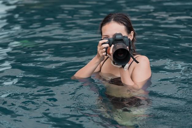 Portrait de femme avec appareil photo reflex numérique, prenant une photo dans l'eau. Photo Premium