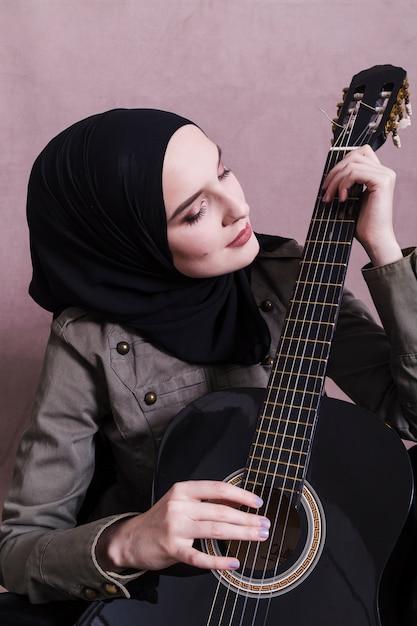 Portrait de femme arabe à la guitare Photo gratuit