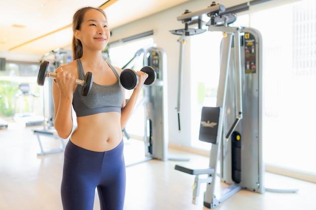 Portrait femme asiatique exerçant et entraînez-vous dans une salle de sport Photo gratuit