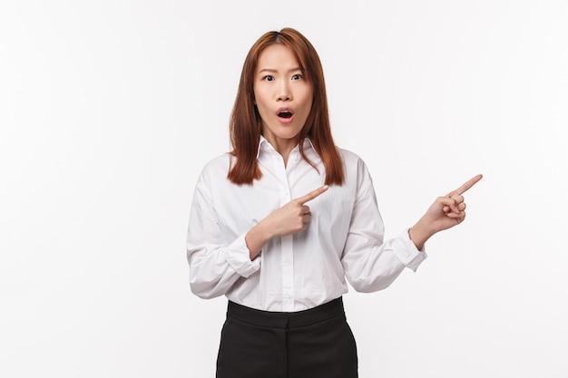 Portrait De Femme Asiatique Gaie Impressionnée En Chemise Blanche, Pointant Les Doigts Vers La Droite Comme Parler De Nouvelles Géniales, Promotion De Nouveaux Produits, Discuter De Potins, Amusé, Mur Blanc Photo Premium