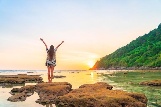 Portrait De Femme Asiatique Sur Le Rocher à Bras Ouverts Au Coucher Du Soleil Autour De L'océan En Vacances Photo gratuit