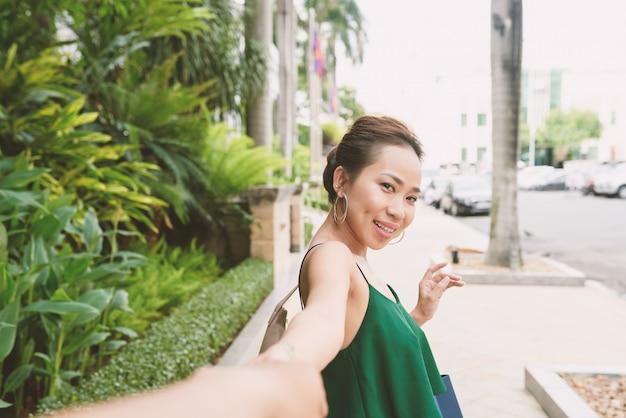 Portrait de femme asiatique se retournant et regardant la caméra en tirant la main de son petit ami méconnaissable Photo gratuit